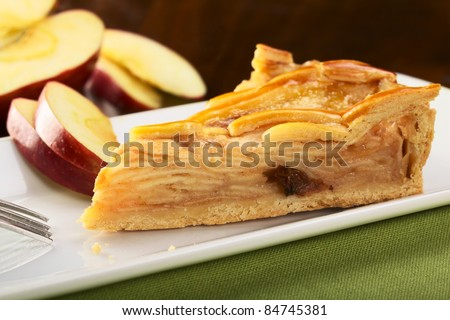 A slice of delicious apple pie with apple slices in the back (Selective Focus, Focus on the left front part)