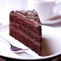 A slice of delicious chocolate cake. Piece of Cake on a Plate. Sweet food. Sweet dessert. Close up.