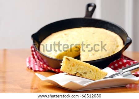 A Slice of Freshly Baked Cornbread on a White Plate with the Cast Iron Pan in the background