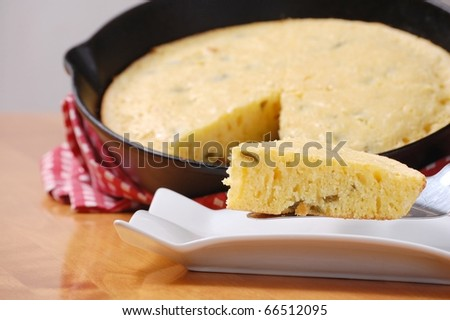 A Slice of Jalapeno Cornbread with the Cast Iron Pan in the Background, on a Wooden Table