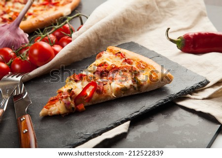 A slice of pizza is on a stone plate around her ingredients closeup