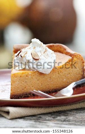 A slice of Pumpkin Cheesecake Pie with homemade whipped cream, alomonds and pumpkin spice. Extreme shallow depth of field.