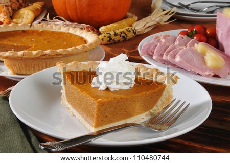 a slice of pumpkin pie on a Thanksgiving dinner table