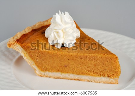 A slice of pumpkin pie topped with a dapple of whipped cream. This image can easily be isolated for insertion anywhere in your design.