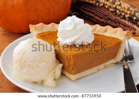 A slice of pumpkin pie with whipped cream and French vanilla ice cream