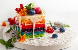 A slice of rainbow cake decorated with fresh berries and flowers for holiday