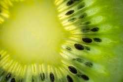 A slice of ripe juicy kiwi closeup. Detailed bright macro photo. The concept of fruit harvest, vegetarianism, useful healthy food, vitamins. Abstract food image.