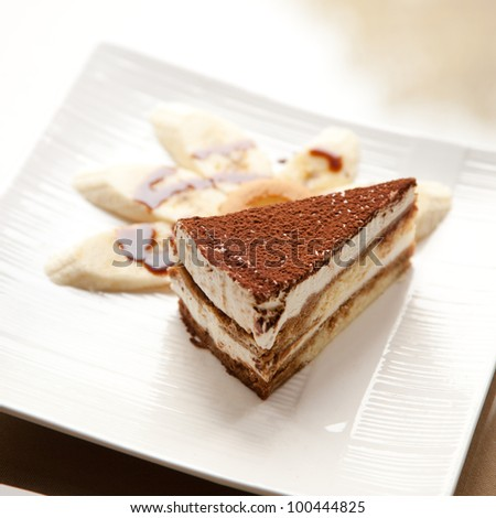 A slice of the Italian delicacy tiramisu and several piece of banana on dish