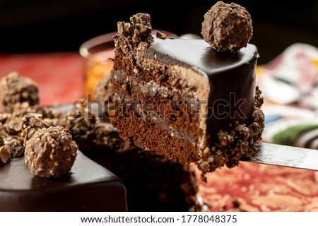 A slice taken off from a chocolate cheese cake on a red table mat Photo stock ©