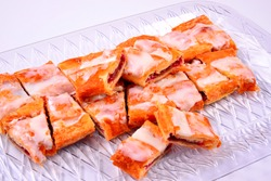 A sliced and laid out batch or raspberry Kringle on a clear tray with a white background. The Kringle is a local favorite in Racine and southeastern Wisconsin.