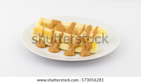 A sliced in half banana on a plate with peanut butter drizzled over the fruit atop a white tablecloth.