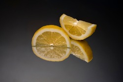 a sliced lemon on a mirror with the black background