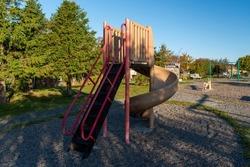 A slide, swing and jungle gym in a children's park, outdoors, made from metal and plastic. The ground in the area is covered in sand with a grass boundary. There are trees in the background.