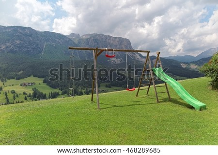 A slide & swing in a playground on a grassy hill with mountains in background & Village La Villa in the valley of Val Badia on a sunny summer day in Dolomites, Bolzano, Alto-Adige, South Tyrol, Italy  #468289685