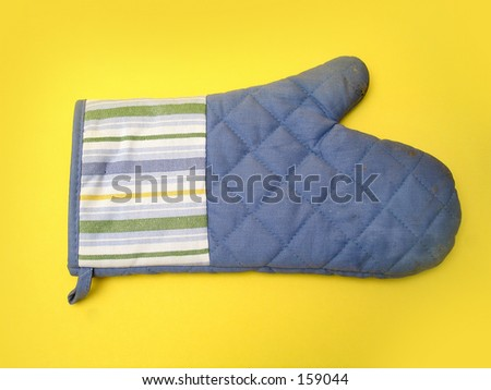 A slightly used oven mitt on a yellow background.