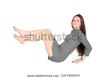 be48262bab A slim beautiful young woman sitting in a gray short dress on the floor  bare feet