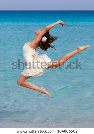 A slim woman is dancing on the beach