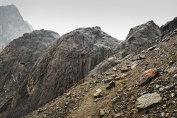 A sloping slope covered with loose stones. Difficult climb to Aktru. Beautiful views of the rounded mountains on a tour of the nature of Altai land. High  pyramidal mountain. Siberia. Russia.