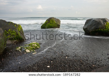 A slow shutter photo of moving waves hitting the shore and rocks on the beach.