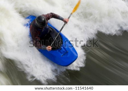 A slow shutterspeed shot of a kayaker in very rough whitewater.