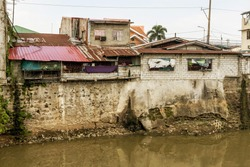 A slum or squatter area along a heavily polluted river bordering Metro Manila and Cavite. Disregard of zoning laws near riverbanks. A polluted river.