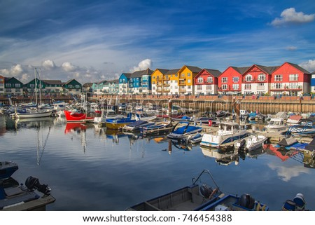 A small and cozy harbor in the town of Exmouth. There are many vessels moored here. Around the harbor are colorful beautiful houses. Devon. England