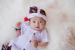 a small and cute baby in white Balinese clothes sleeping on a white blanket