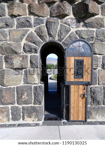 A small arched doorway in Roosevelt Arch leading to Yellowstone National Park                             #1190130325
