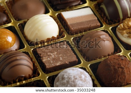 A small assortment of chocolate truffles and pralines in a box.  Very Shallow depth of field, focusing across the middle.