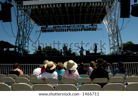 A small audience listens to a band's sound check