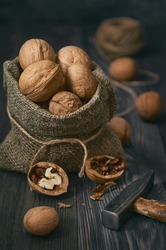 A small bag of walnuts on a dark wooden table, chopped nuts and an old hammer next to it. Vertical orientation.