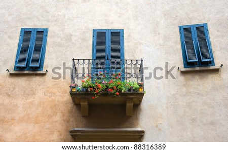A small balcony on a house, and blue painted shutters at the mediterranean sea.