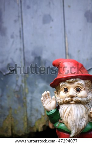 A small bearded garden gnome waving his hand. Set against a soft focus wooden garden shed door.