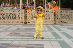 a small, beautiful blond boy in a yellow suit, an orange cap and glasses plays a toy pipe in an amusement park