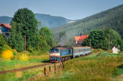 A small beautiful passenger train with two carriages on a background of green mountain peaks and slopes departs from the station. Spring photo of railway in the mountains with grass and flowers