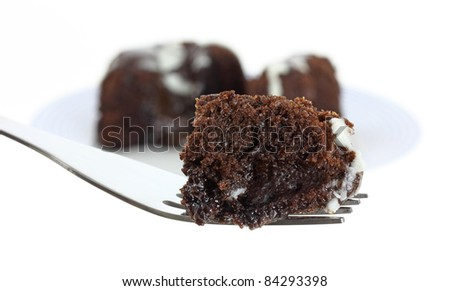A small bite of chocolate lava cake on a fork with the remainder of the cake in the background.
