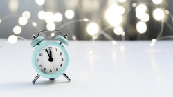 A small blue alarm clock shows 12 o'clock, stands on a light table with a blurred background and bokeh lights. Christmas and New Year concept.