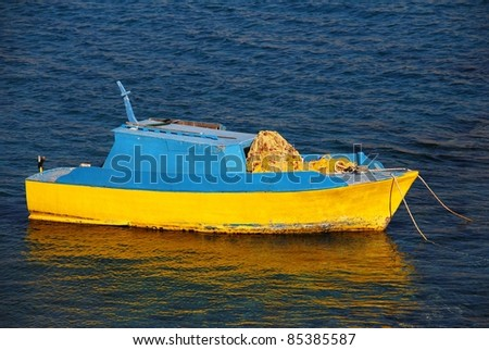 A small blue and yellow wooden fishing boat moored off the coast at Emborio on the Greek island of Halki.