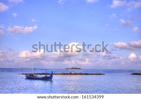 A small blue boat peacefully rests on smooth waters.