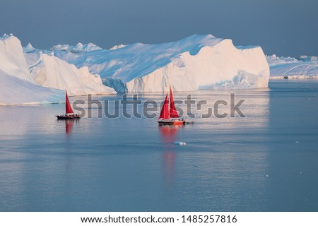 A small boat among icebergs. Sailboat cruising among floating icebergs in Disko Bay glacier during midnight sun Ilulissat, Greenland. Studying of a phenomenon of global warming Ices and icebergs #1485257816