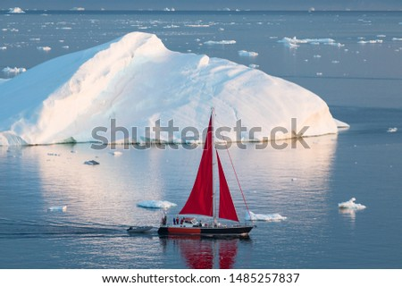 A small boat among icebergs. Sailboat cruising among floating icebergs in Disko Bay glacier during midnight sun Ilulissat, Greenland. Studying of a phenomenon of global warming Ices and icebergs #1485257837