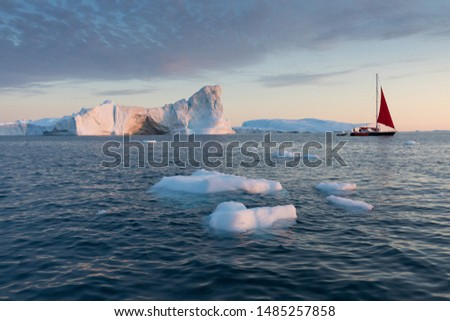 A small boat among icebergs. Sailboat cruising among floating icebergs in Disko Bay glacier during midnight sun Ilulissat, Greenland. Studying of a phenomenon of global warming Ices and icebergs #1485257858