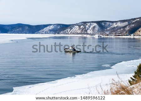 A small boat at the source of the Angara River from Lake Baikal in winter. Baikal port is visible on the opposite bank.  #1489596122