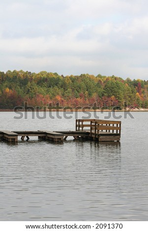 A small boat dock on a calm lake in early Autumn.