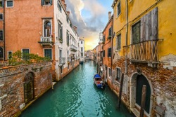 A small boat docks in the emerald green water of a colorful canal in a residential area, as the sun sets under storm clouds in Venice, Italy.