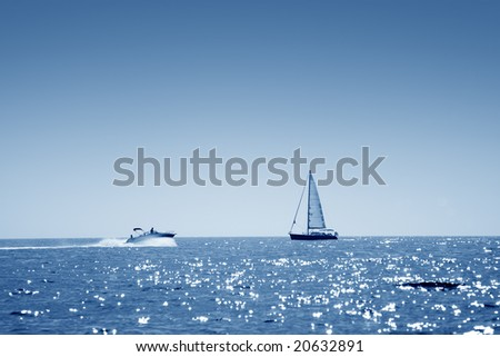 A small boat facing a motor boat on open sea