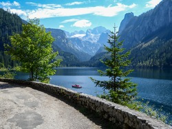 A small boat floating on Gosau lake, with Dachstein glacier in the back in Austrian Alps. The lake is surrounded by high mountains, overgrown with tall trees. Sun reflects on the surface. Serenity