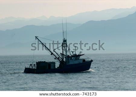 Ein kleines Boot geht in die nebelige Katchemak Bucht voran.