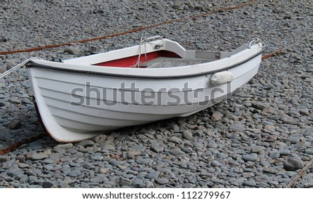 A Small Boat Moored on a Shingle Pebble Beach.
