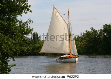 A small boat tacks across the winds on the Norfolk Broads